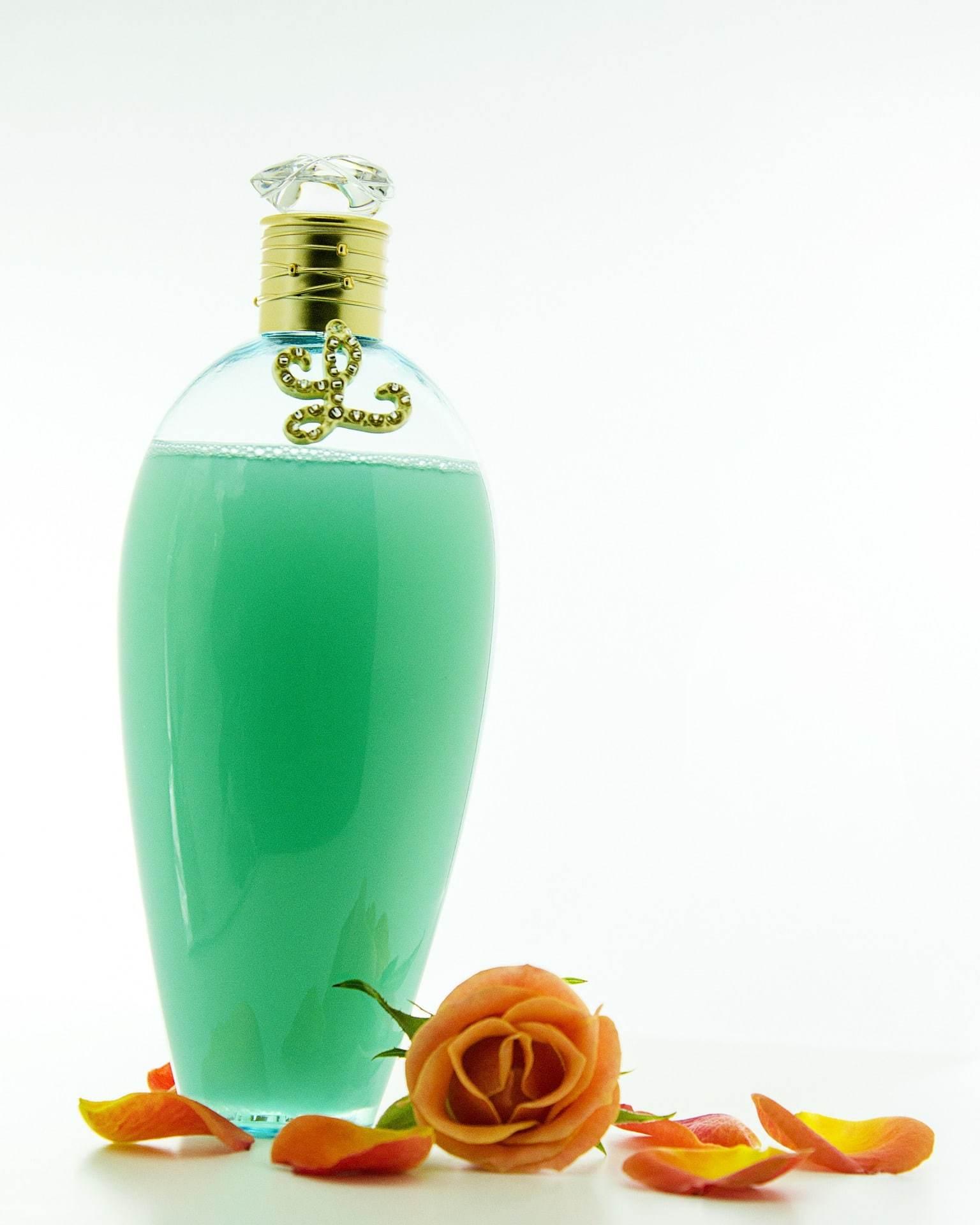 Intim. A képen egy üveg zöld sampon látható, mellete narancssárga rózsaszirmokkal
